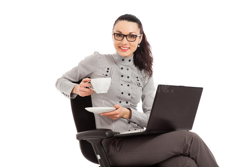 Coffe de consumición de la muchacha morena, sentándose en la silla con el ordenador portátil foto de archivo
