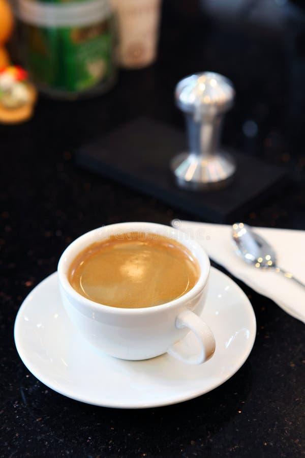 Coffe de Creammy dans la tasse blanche sur le plat avec le fond foncé photo libre de droits