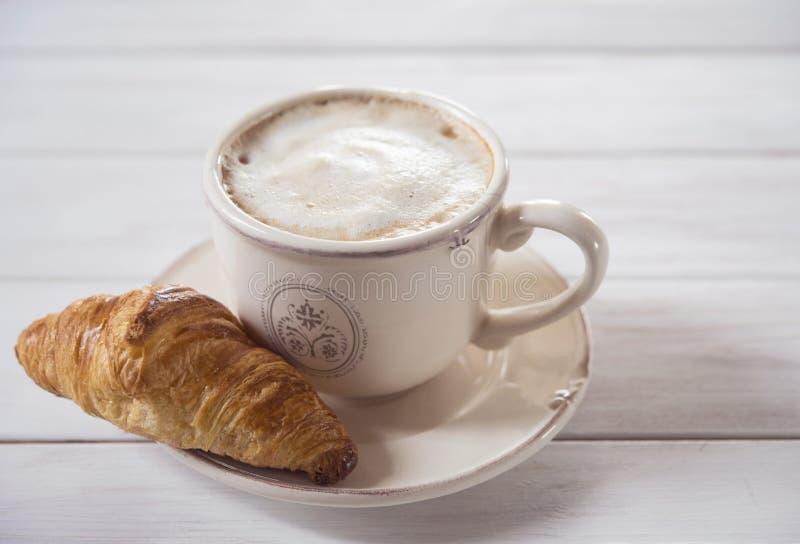 Coffe e forno di legno di cappuchino della prima colazione di mattina del fondo del croissant rustico immagini stock