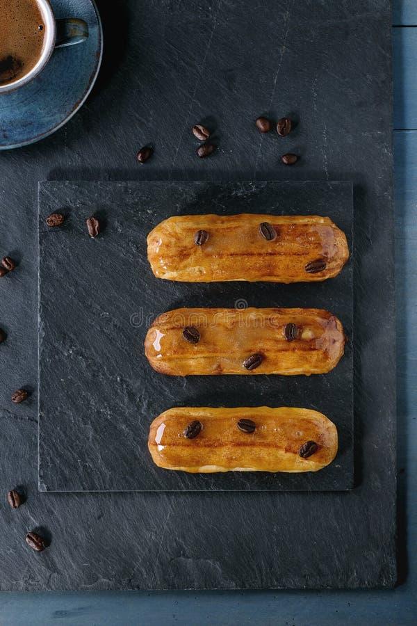 Coffe eclairs με το φλιτζάνι του καφέ στοκ εικόνα με δικαίωμα ελεύθερης χρήσης