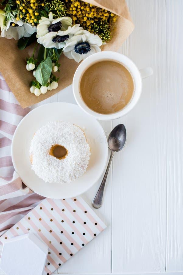 Coffe et un beignet avec les fleurs fraîches images stock