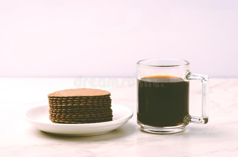 Coffe exponeringsglas med kakor på vitt marmorbakgrund/Coffe exponeringsglas med kakor på vit marmorbakgrund Selektivt fokusera t arkivbild