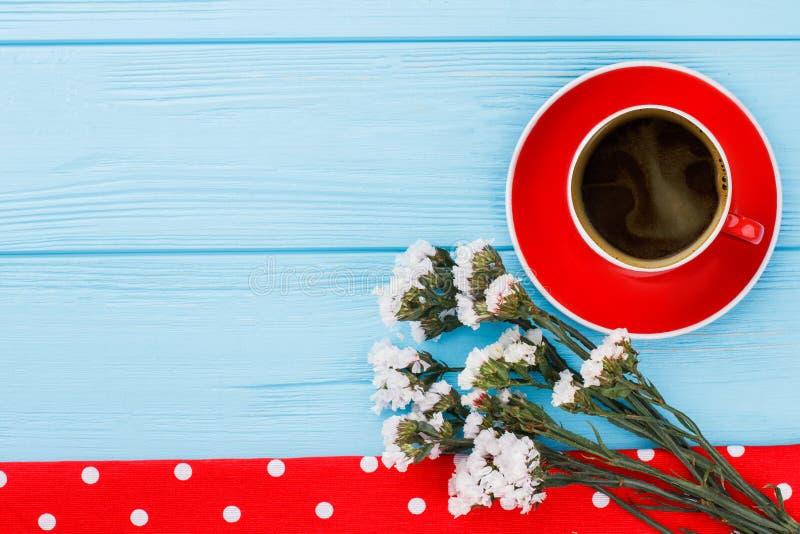 Coffe kopp, vita staticeblommor och prickig handduk royaltyfri bild