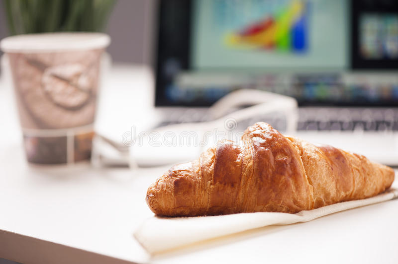 Coffe, laptop and croissant stock images