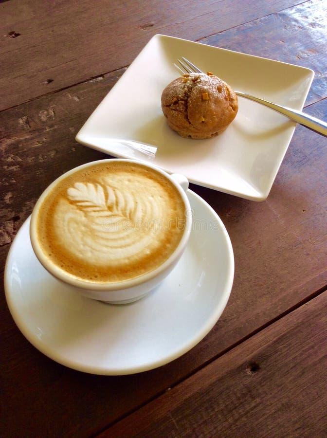 Coffe-Lattekunst auf hölzerner Tabelle stockbilder