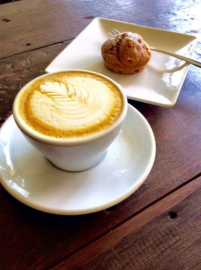 Coffe-Lattekunst auf hölzerner Tabelle lizenzfreies stockfoto