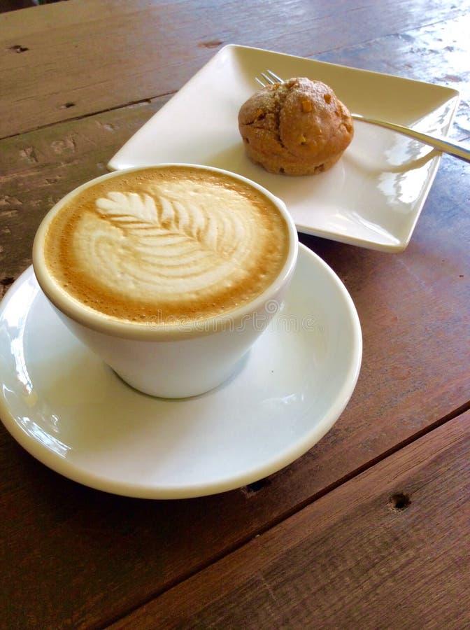 Coffe-Lattekunst auf hölzerner Tabelle lizenzfreie stockbilder