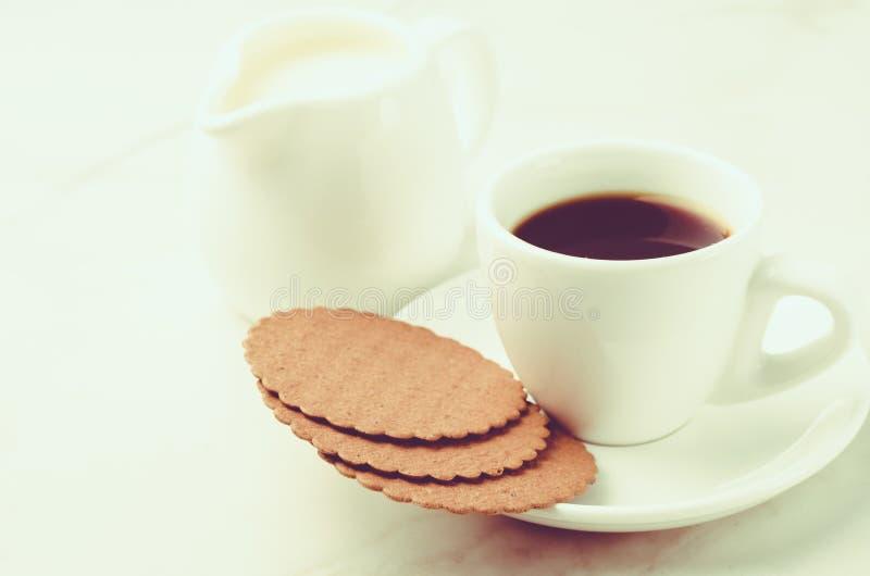 Coffe mjölkar mjölkar den vita koppen med kakor och/Coffe den vita koppen med kakor och på vit marmorerar bakgrund Selektiv fokus royaltyfri bild