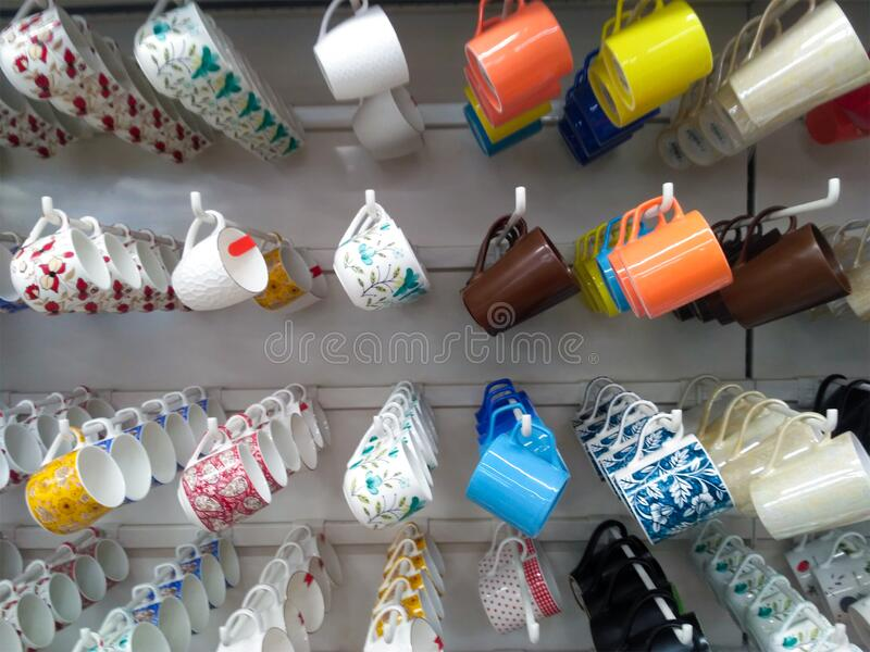 Coffe Mugs. Colorful coffe mugs hanging in a super store. Lots of tea mugs or coffe mugs background hanging in super market stock images