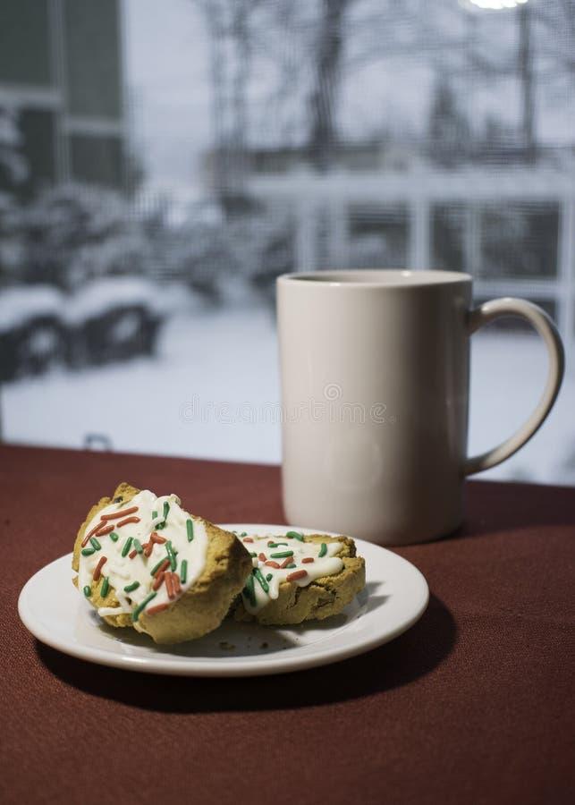 Coffe och Biscotti framme av fönstret på snöig dag fotografering för bildbyråer