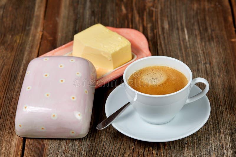 Coffe och smör på en maträtt på en träbrunt royaltyfri fotografi