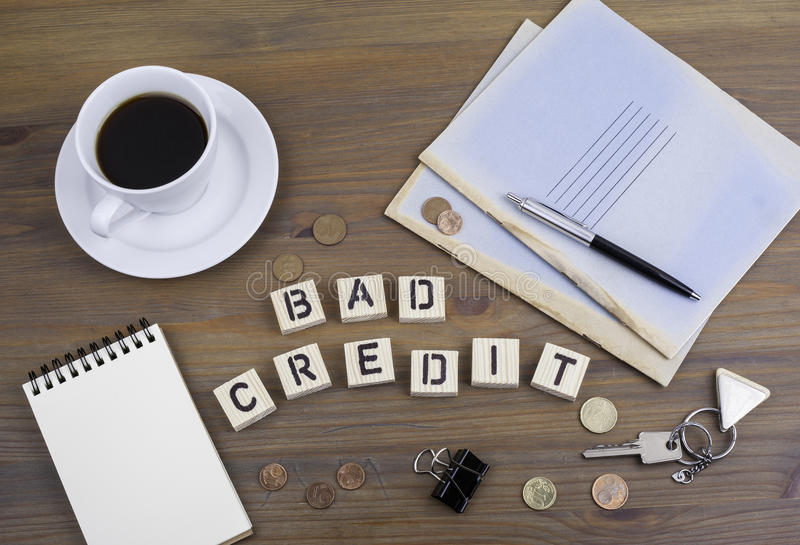 Coffe, Stift, Geld und blocknot auf einem Schreibtisch und einem Text Schlecht-Kredit stockbilder