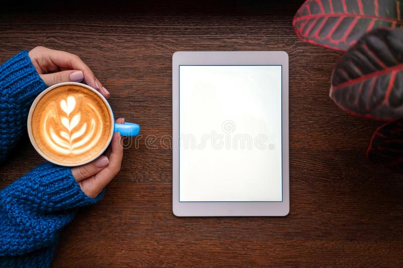 Coffe and tablet. A cup of cappuccino with latte art in woman`s hands with perfect manicure and a tablet with screen on on the wood table royalty free stock photo