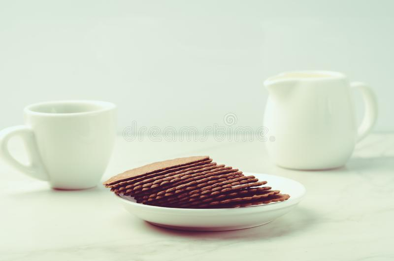 Coffe white cup with cookies and milk/breakfast in white ceramic ware and cookies on white background. Selective focus stock photo