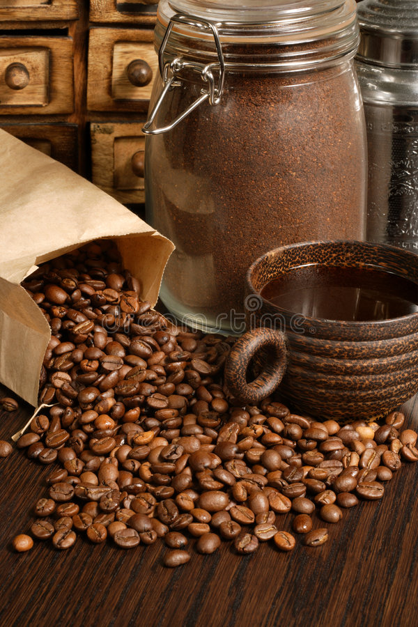 Coffee. Image of roasted coffee beans, coffee cup, and ground beans on a wooden table royalty free stock image
