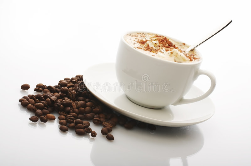 Coffee. Cup with cream top on the plate with  beans stock images