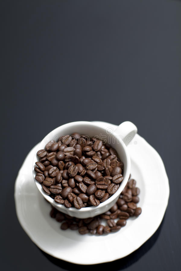 Coffee 5. A white ceramic coffee cup and saucer against a black background filled with whole coffee beans stock image