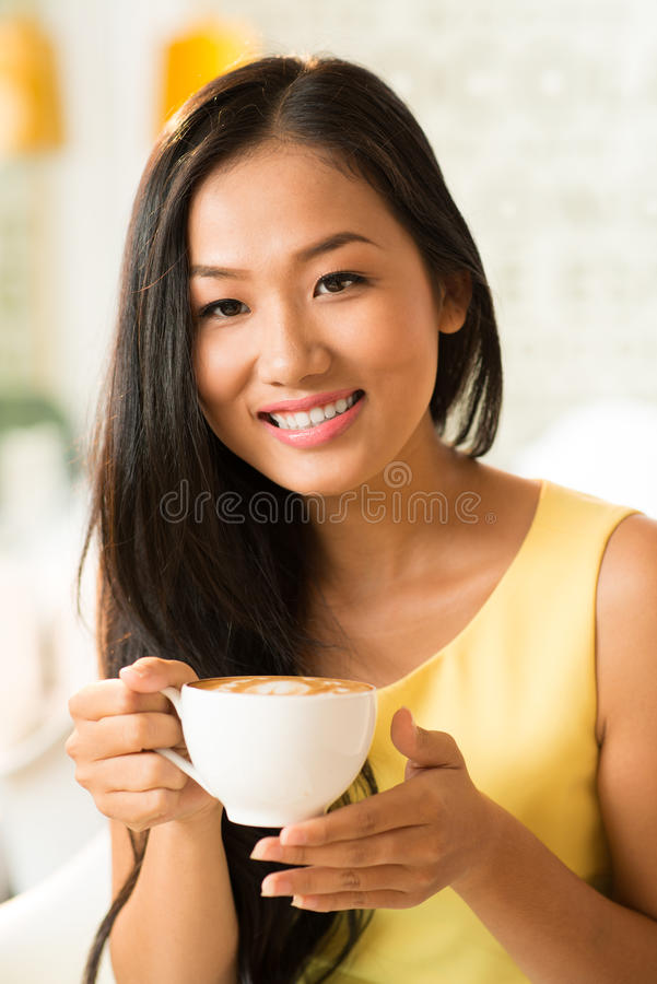 Coffee addict. Close-up portrait of a lovely female coffee addict drinking latte at a cafeteria royalty free stock photo