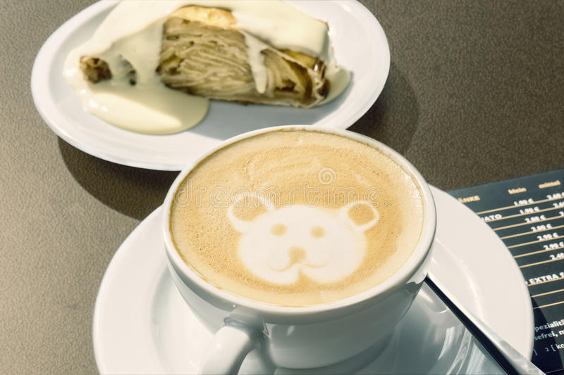 Coffee with Apfelstrudel. Cappuccino with little bear decoration drawn into the foam. In the background the austrian specialty Apfelstrudel with vanilla sauce royalty free stock photos