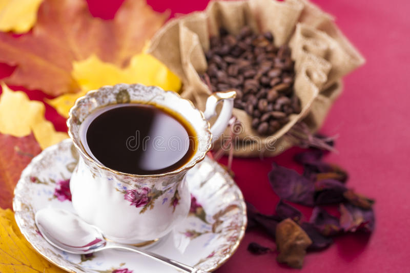 Coffee. Autumn style close up photo of a hot coffee porcelain cup with the bag of the coffee beans over a red background royalty free stock image
