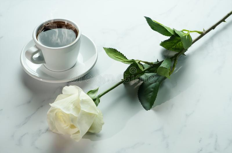 Coffee background of a cup of hot black coffee with bunch of white rose on white marble background.  stock images