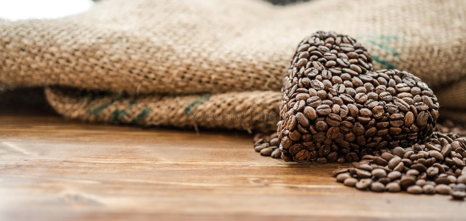 Coffee bag and heart from coffee beans on table royalty free stock photo