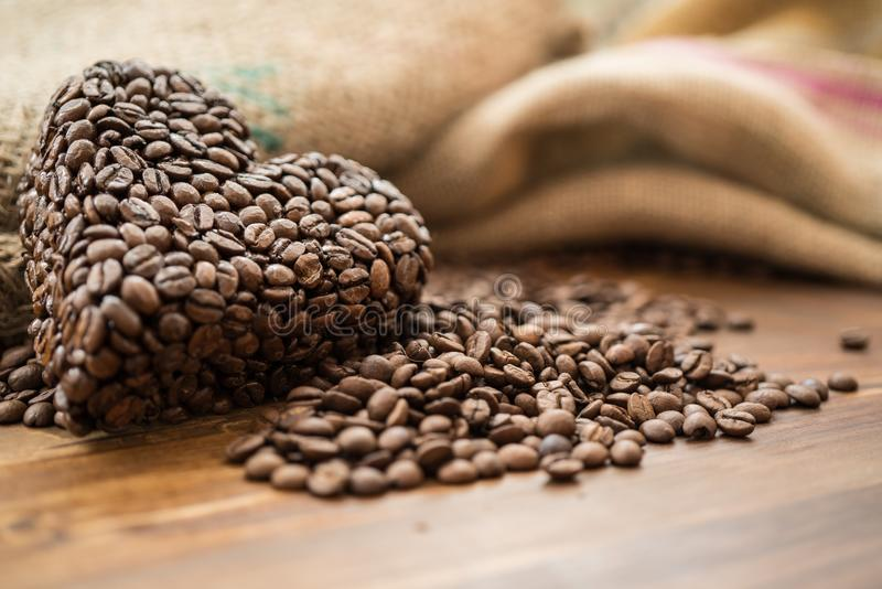 Coffee bag and heart from coffee beans on table stock photography