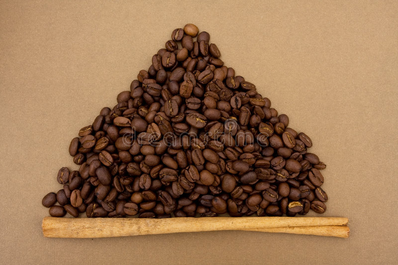 Coffee Bean Border. A mountain of coffee beans with a cinnamon stick sitting on a brown background, coffee bean border royalty free stock photos