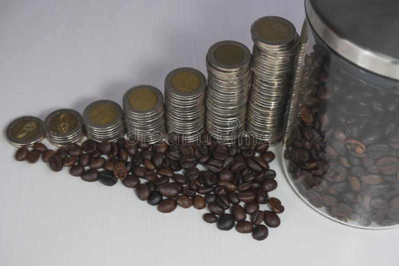 Coffee bean in glass bottle with coins graph, business growth concept royalty free stock photos