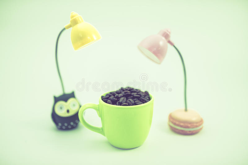 The coffee bean in green cup with LED lamps, white background, s royalty free stock image