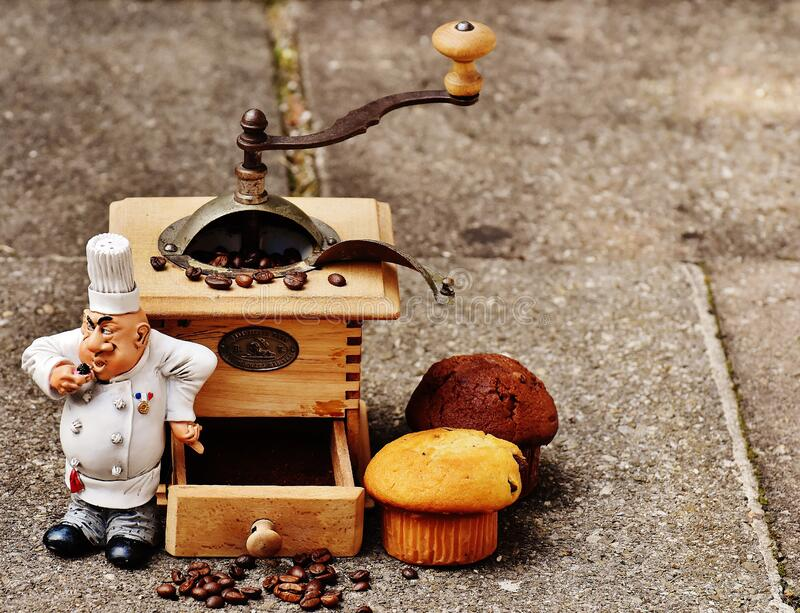 Coffee bean grinder and muffins stock photos
