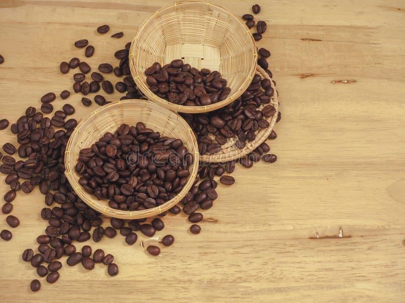 Coffee bean in little basket on slat wood.  royalty free stock image