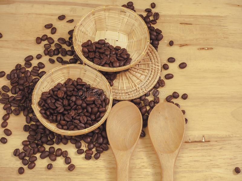 Coffee bean in little basket and spoon wood on slat wood.  stock photo