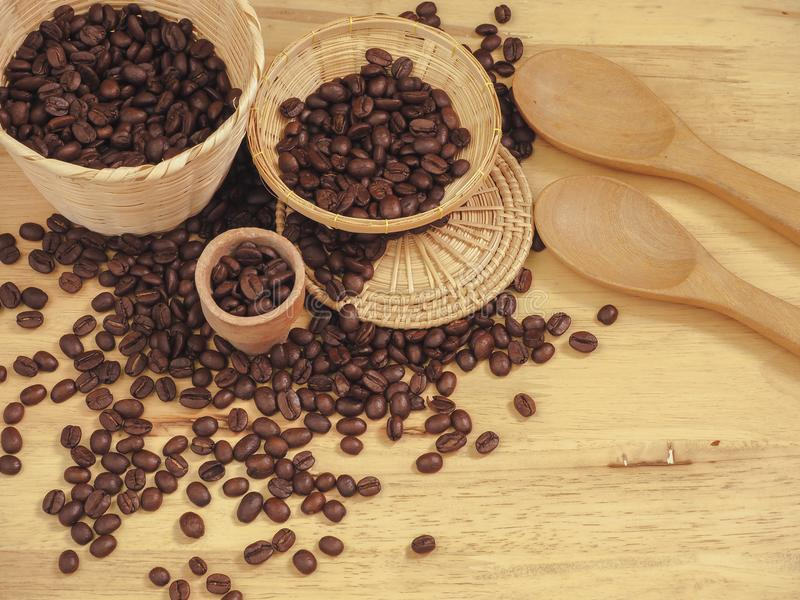 Coffee bean in little basket and spoon wood on slat wood.  royalty free stock photos