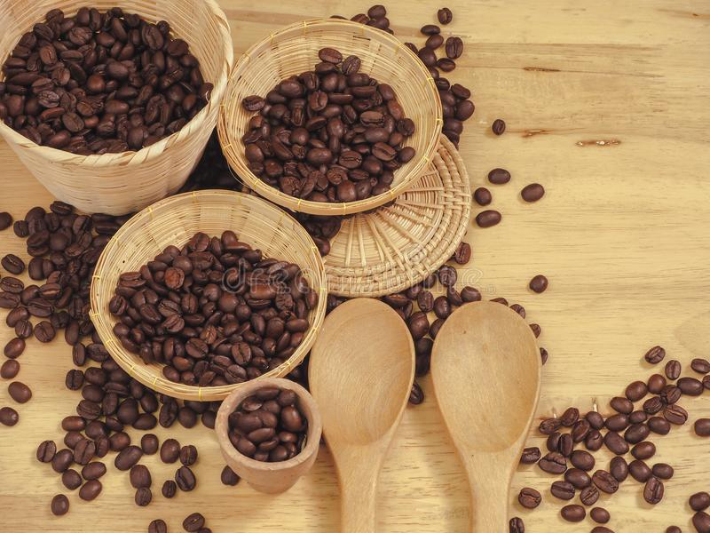 Coffee bean in little basket and spoon wood on slat wood.  stock photos
