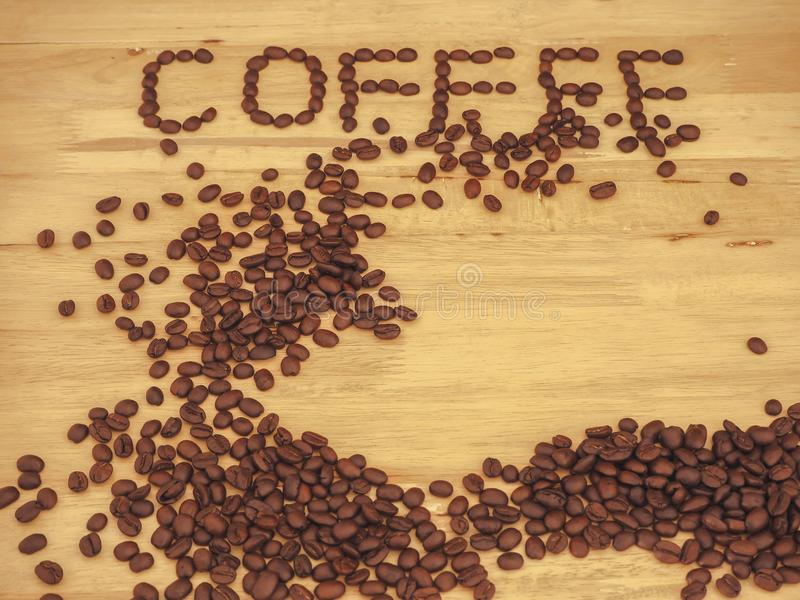 Coffee bean on slat wood and write coffee.  royalty free stock photography