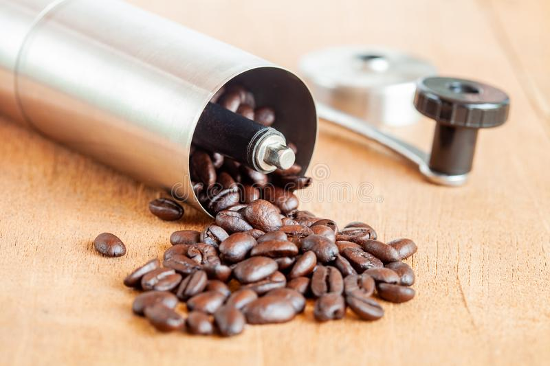 Coffee bean spill out of Coffee grinder on wood. Coffee bean spill out of Coffee grinder on old wood royalty free stock photos