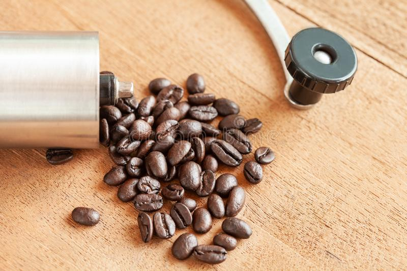 Coffee bean spill out of Coffee grinder on wood. Coffee bean spill out of Coffee grinder on old wood stock images