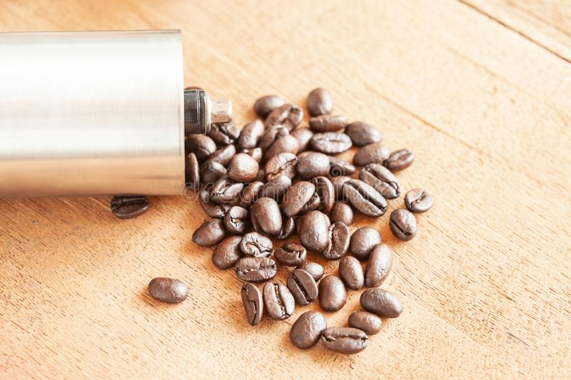 Coffee bean spill out of Coffee grinder on wood. Coffee bean spill out of Coffee grinder on old wood royalty free stock image