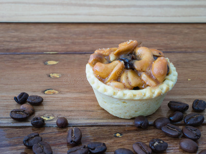 Coffee bean and tart on wood background. Coffee bean and cashew nuts tart on wood background stock images