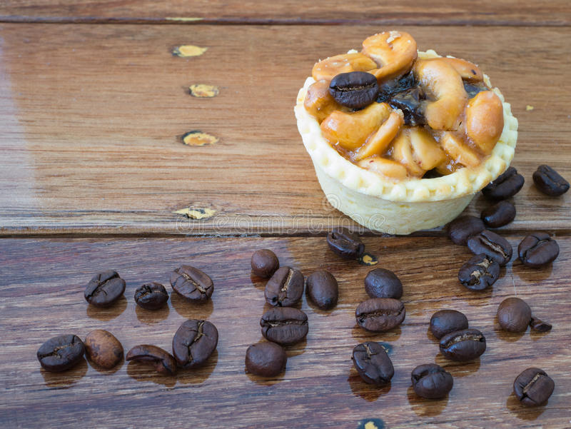 Coffee bean and tart on wood background. Coffee bean and cashew nuts tart on wood background royalty free stock photography
