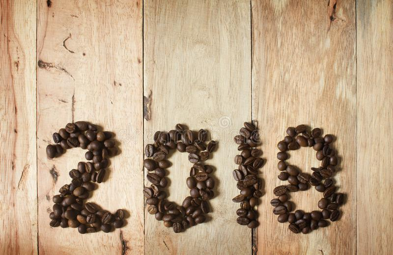 2018 coffee bean text on wood background, new year concept royalty free stock photo