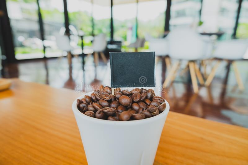 Coffee bean in white ceramic cup and black flag with brown wooden background royalty free stock photography