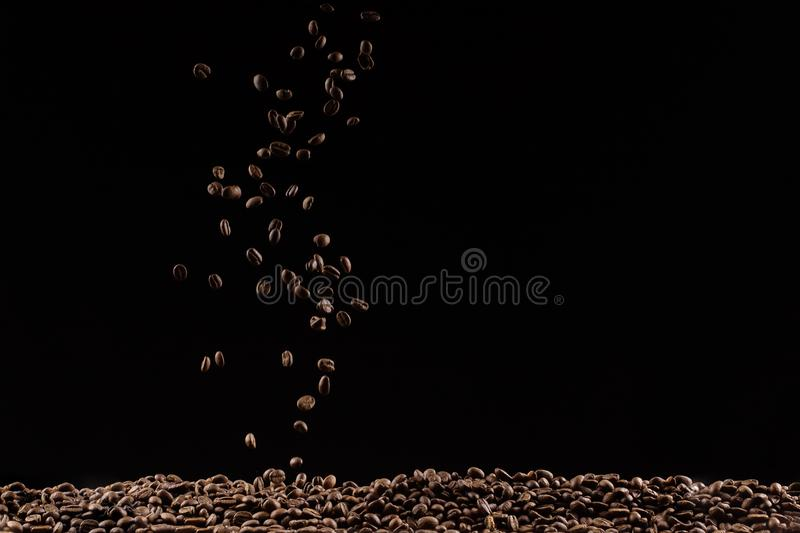 Coffee beans in the air flying in flight like a spray. On a black background, coffee shop advertising concept, copy space. Coffee beans in the air flying in stock photo