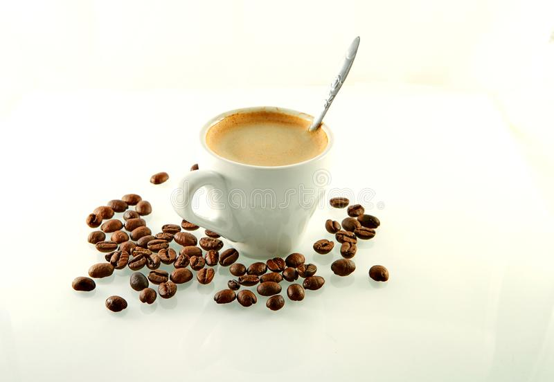 Coffee beans around a coffee cup with espresso coffee on a white. Background, agriculture, arabic, aroma, aromatic, beverage, black, breakfast, brown, cafe stock photo