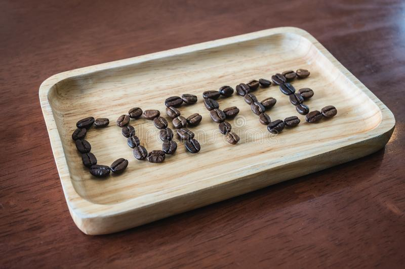 Coffee beans arranged text ` Coffee ` on wooden tray on wood table. stock photos