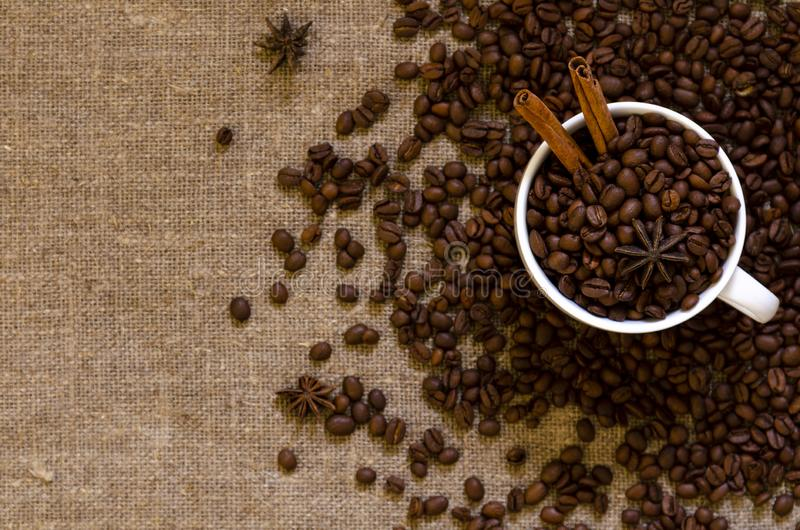 Coffee beans and badian on cup on the sackcloth background stock photo
