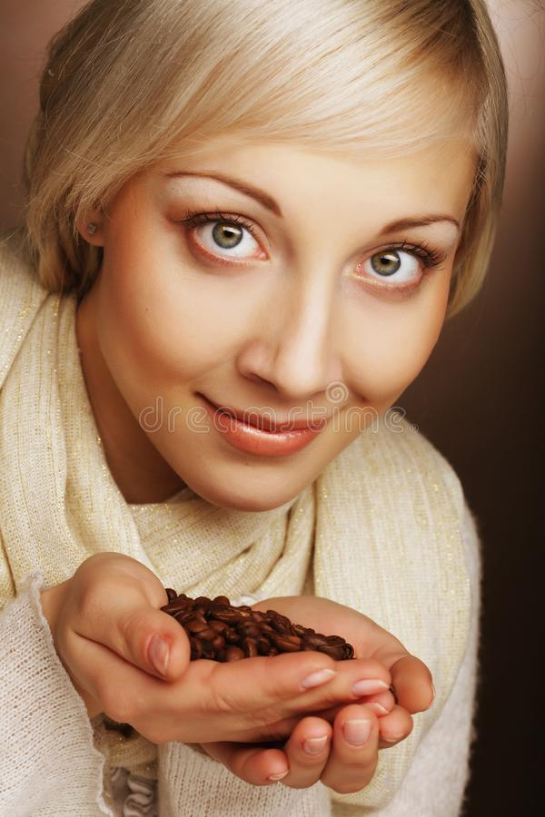 Beautiful blond woman smelling coffee beans. stock images