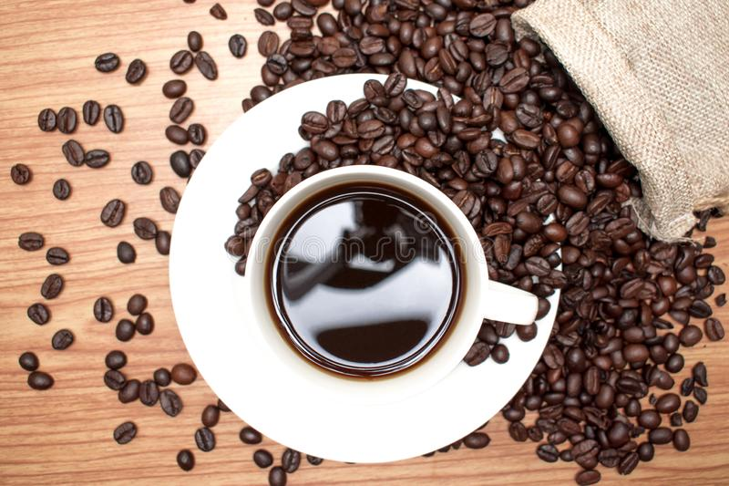 Coffee beans with black coffee on a brown wood background, top view royalty free stock photography