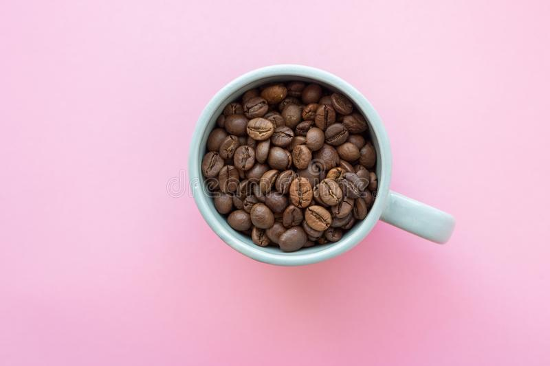 Coffee beans in blue cup on pink background view from above. Breakfast concept. Cafe concept. royalty free stock image